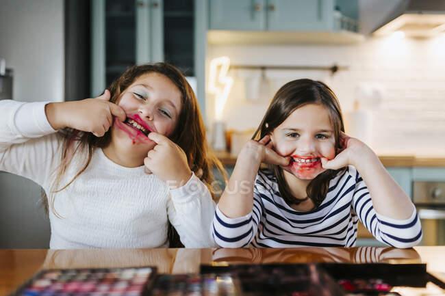 Ragazze giocose con il trucco sul viso prendere in giro mentre seduti al tavolo da pranzo in cucina domestica — Foto stock