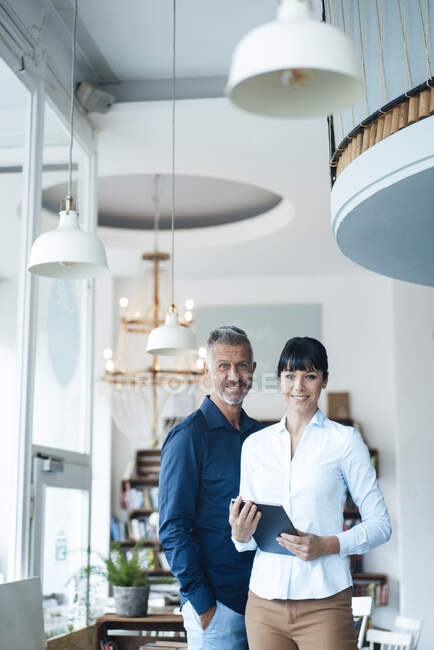 Деловая пара, стоящая вместе в кафе — стоковое фото