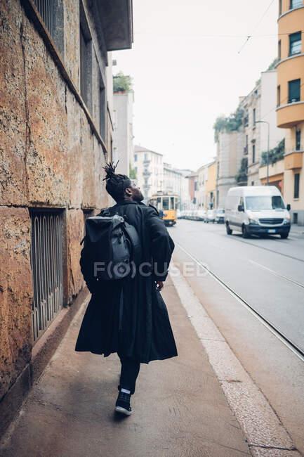 Jovem com mochila andando na estrada — Fotografia de Stock
