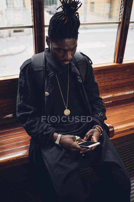 Jovem usando telefone celular enquanto sentado em bonde — Fotografia de Stock
