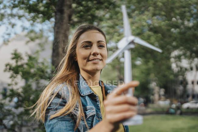 Девушка смотрит на модель ветряной турбины — стоковое фото