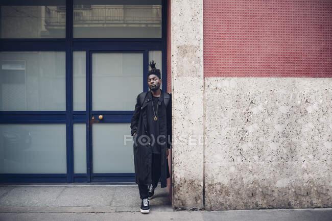 Jovem com a mão no bolso apoiado na parede — Fotografia de Stock