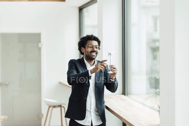 Улыбнитесь мужчина профессиональный осмотр модели ветряной турбины во время пребывания в офисе — стоковое фото