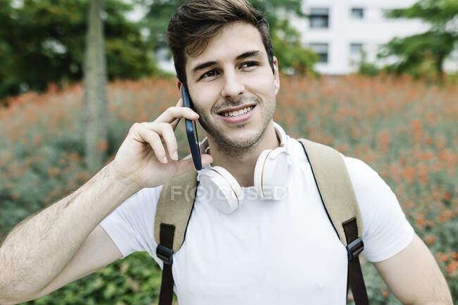 Улыбающийся молодой человек смотрит в сторону, разговаривая по смартфону — стоковое фото