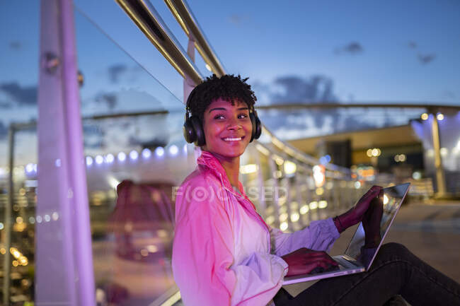 Женщина с ноутбуком смотрит в сторону, слушая музыку на наушниках — стоковое фото