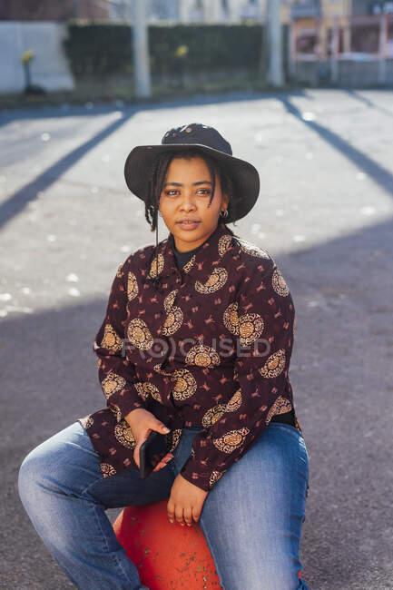Mulher usando chapéu segurando telefone celular enquanto sentado no caminho — Fotografia de Stock