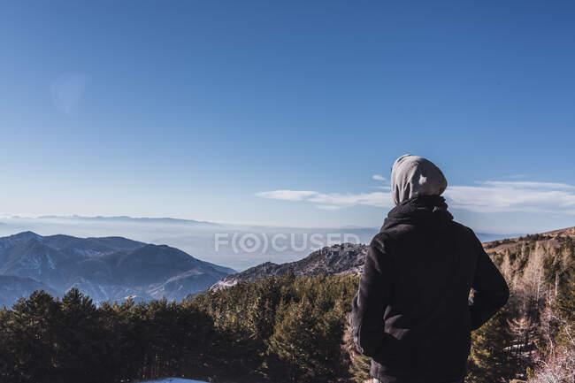 Человек в теплой одежде смотрит на вид зимой — стоковое фото