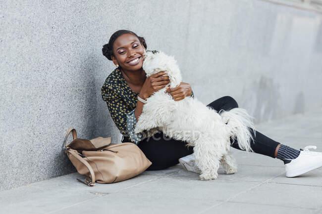 Улыбающаяся женщина, играющая с собакой, сидя на тропинке — стоковое фото