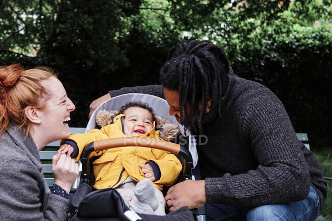 Pais felizes brincando com o filho sentado no carrinho no parque — Fotografia de Stock
