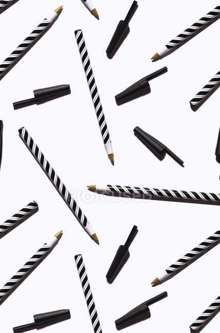 Patrón de plumas a rayas blancas y negras planas sobre fondo blanco - foto de stock