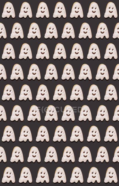 Patrón de galletas de chocolate en forma de fantasma planas colocadas sobre fondo negro - foto de stock