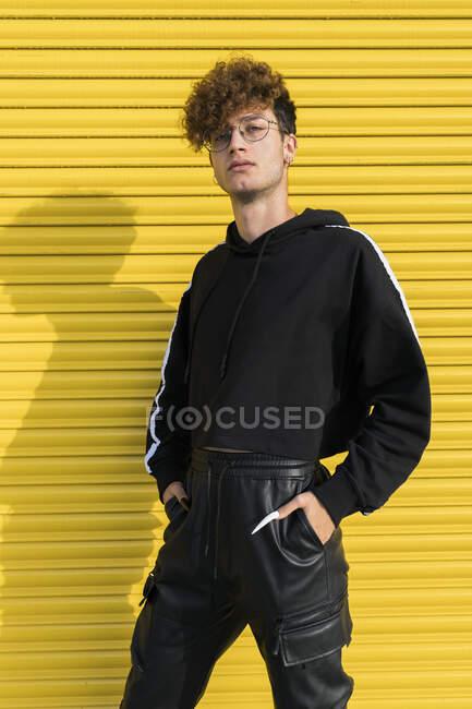 Молодой человек с руками в карманах за затвором — стоковое фото