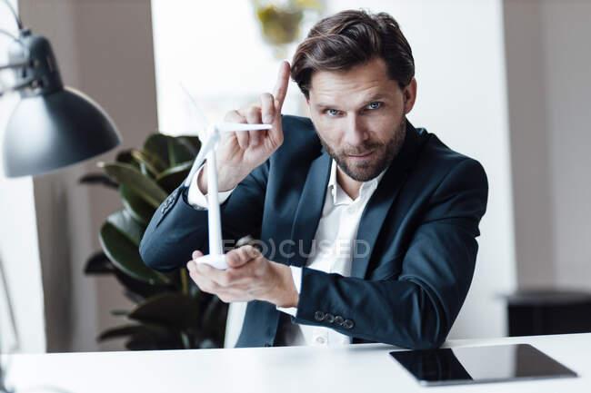 Зрелый бизнесмен указывает на то, что держит модель ветряной турбины в офисе — стоковое фото