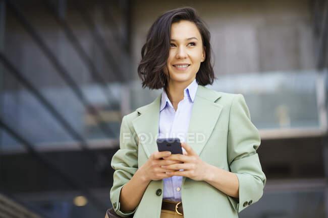 Улыбающаяся деловая женщина смотрит в сторону, держа смартфон снаружи офисного здания — стоковое фото