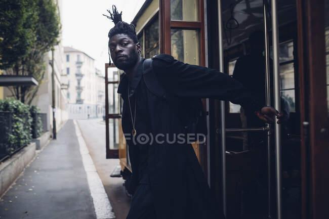 Homem olhando para longe enquanto pendurado em trilhos de eléctrico — Fotografia de Stock