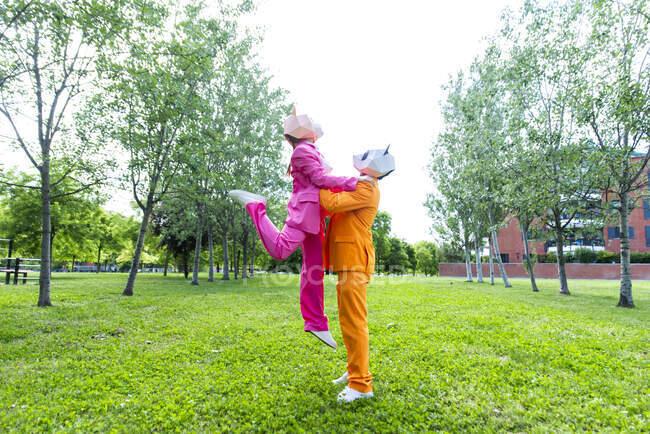 Взрослая пара в ярких костюмах и масках животных, играющая в общественном парке — стоковое фото