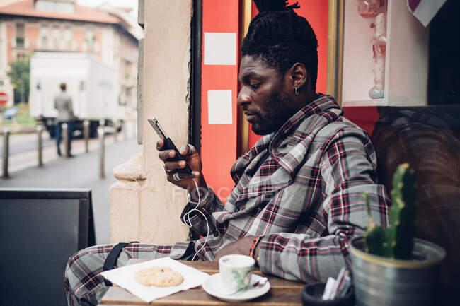 Jovem elegante usando telefone celular no café da calçada — Fotografia de Stock