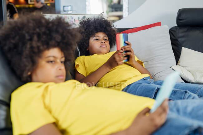 Братья-близнецы используют беспроводные технологии на диване дома — стоковое фото