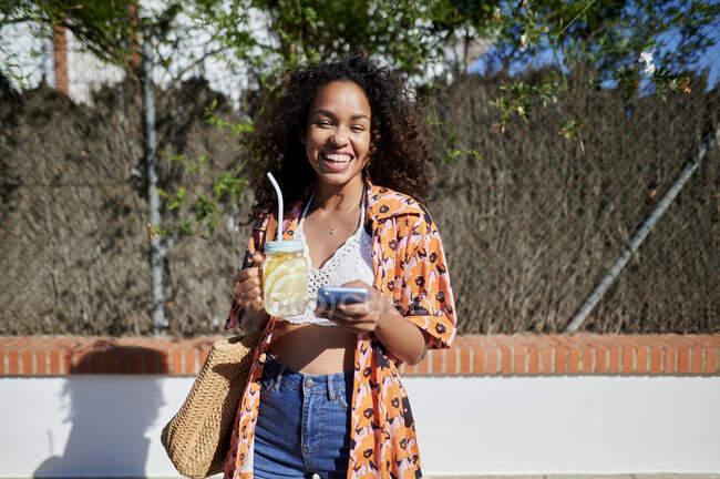 Усміхнена жінка з лимонадом і смартфоном у сонячний день. — стокове фото