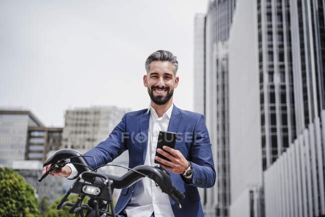 Бизнесмен с мобильным телефоном и арендованным велосипедом в городе — стоковое фото