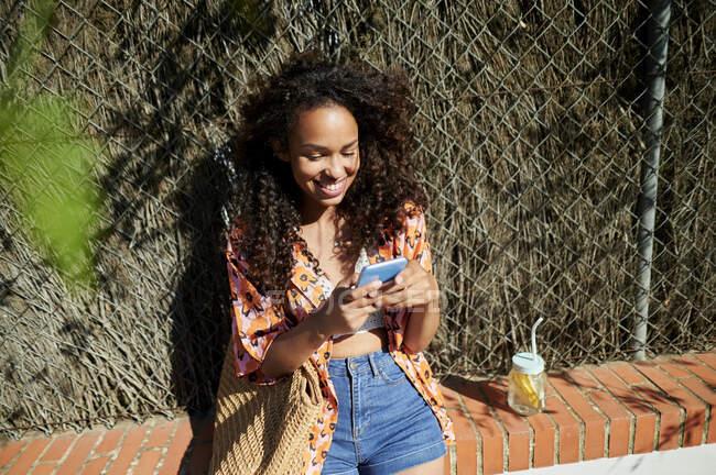 Усміхнена жінка користується розумним телефоном, сидячи на стіні. — стокове фото