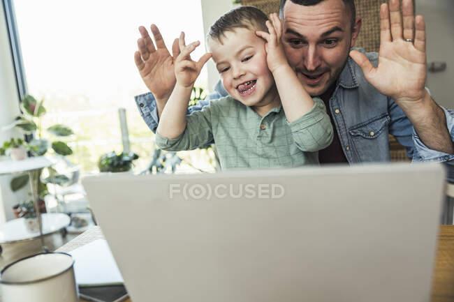 Malizioso padre e figlio prendere in giro mentre seduto con il computer portatile a casa — Foto stock