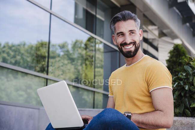 Улыбающийся бизнесмен с ноутбуком отворачивается — стоковое фото