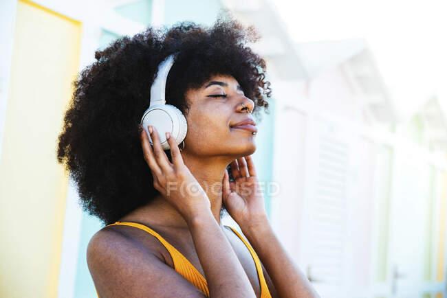Расслабленная афро-женщина слушает музыку через наушники — стоковое фото