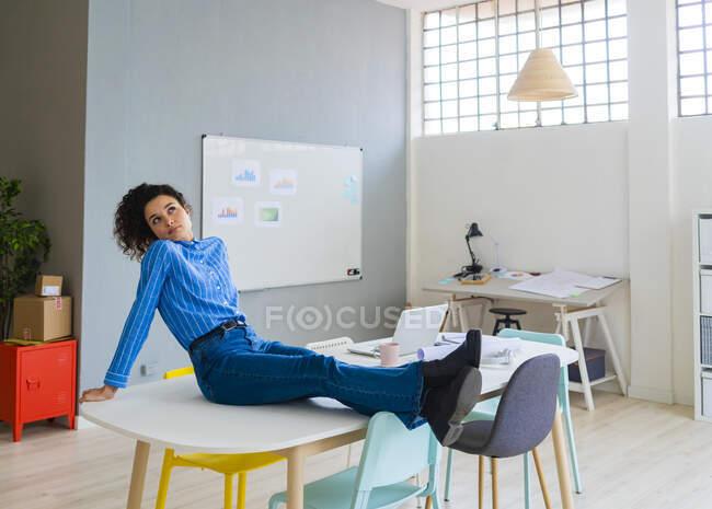 Задумчивая деловая женщина сидит со скрещенными ногами на лодыжке в офисе — стоковое фото