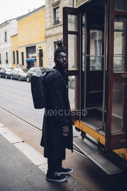 Homem elegante com mochila de pé de bonde no caminho — Fotografia de Stock