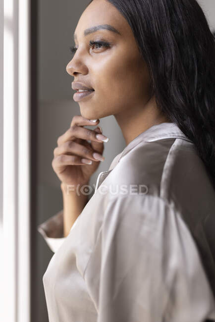 Молодая женщина смотрит в окно дома — стоковое фото