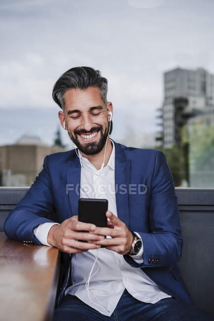 Мужчина-предприниматель с наушниками, использующий мобильный телефон за столом — стоковое фото