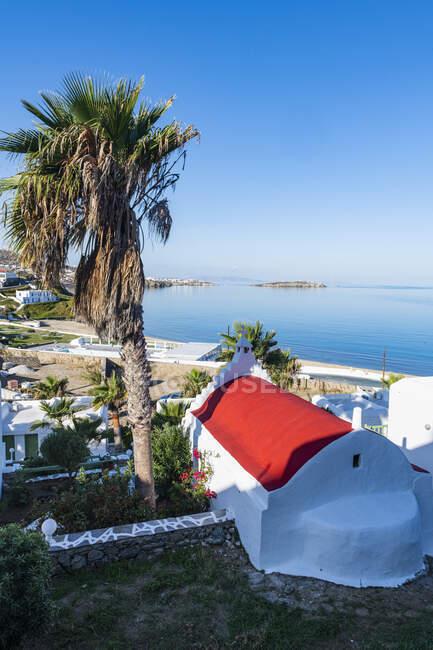 Греция, Южное Эгейское море, Орта, чистое небо над пальмами и прибрежными городскими домами — стоковое фото