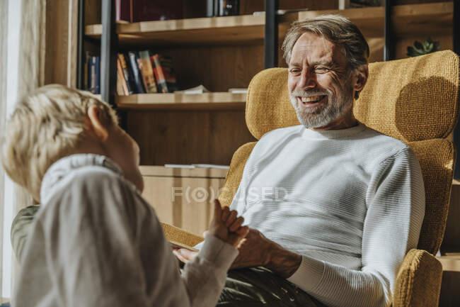 Мужчина смеется, глядя на сына в гостиной — стоковое фото