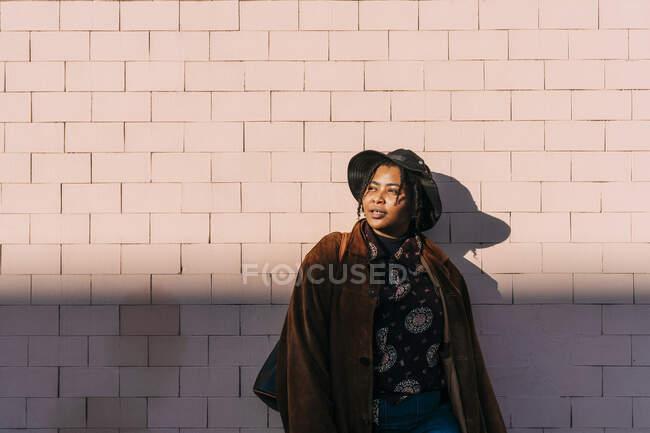 Mulher cuidadosa com chapéu em pé na frente da parede de tijolo — Fotografia de Stock