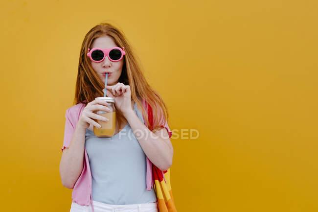 Жінка п'є сік з глечика для каменю перед жовтою стіною. — стокове фото