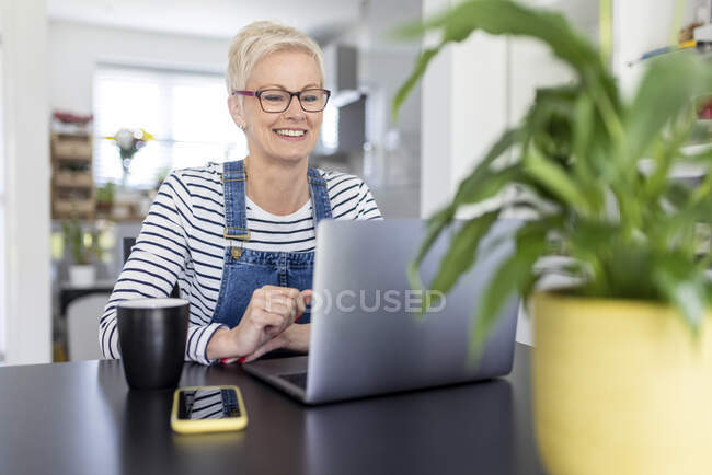 Smiling businesswoman looking at laptop on desk in home office — Stock Photo