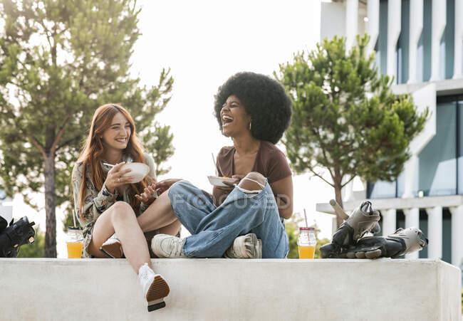 Африканка сміється, сидячи з подругою на лавці. — стокове фото