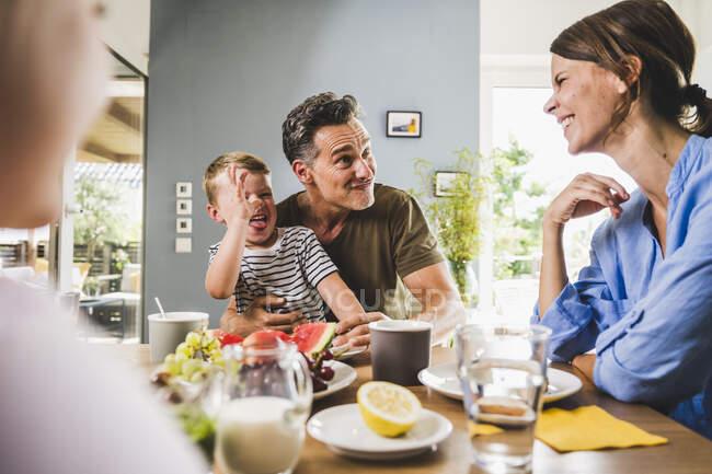 Padre giocoso e figlio prendere in giro la donna mentre fanno colazione a casa — Foto stock