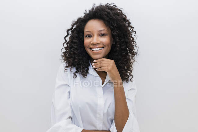 Afro woman with hand on chin over white background — Stock Photo