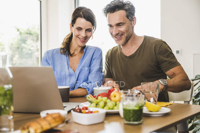 Man and woman watching laptop while having breakfast at home — Stock Photo