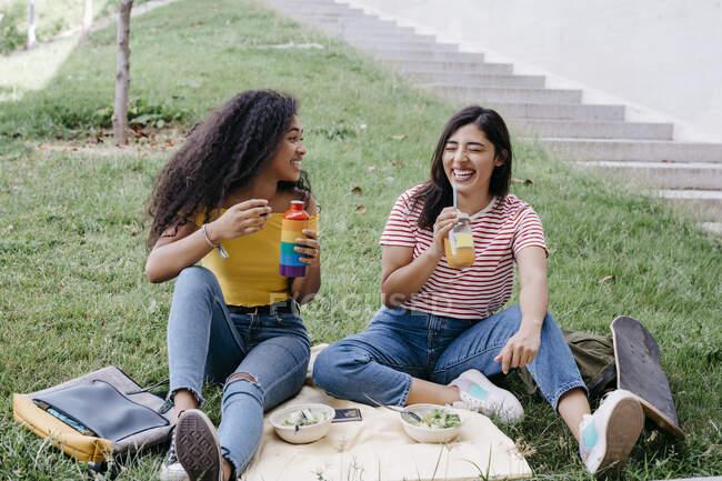 Молода жінка, яка дивиться на подругу, сміється, коли п