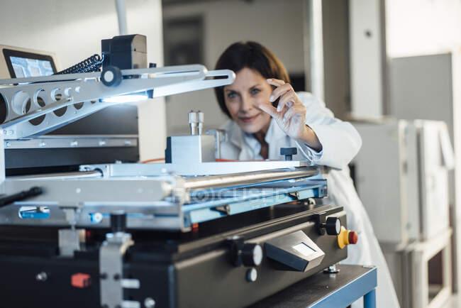 Mature female technician analyzing machinery at industry — Stock Photo