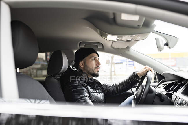 Hipster homme en veste voiture de conduite tout en regardant loin — Photo de stock