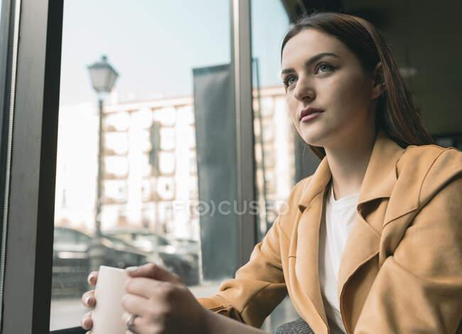 Beautiful woman sitting by glass window at coffee shop — Stock Photo