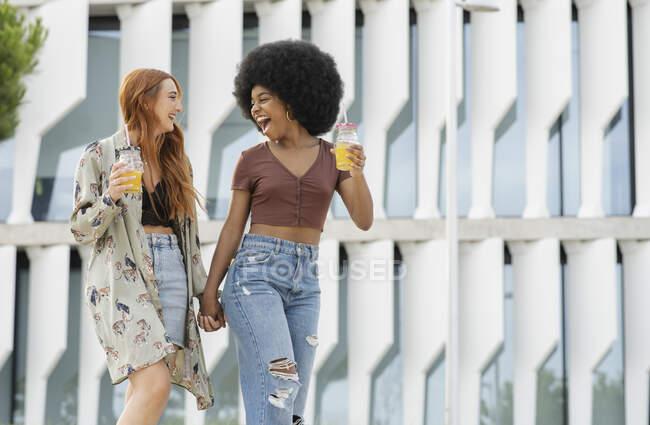 Веселі подружки тримаються за руки, коли ходять містом. — стокове фото