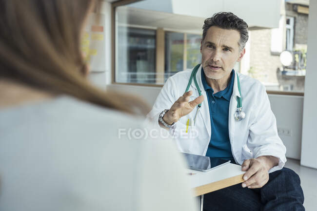 Male doctor explaining female patient while sitting in office — Stock Photo