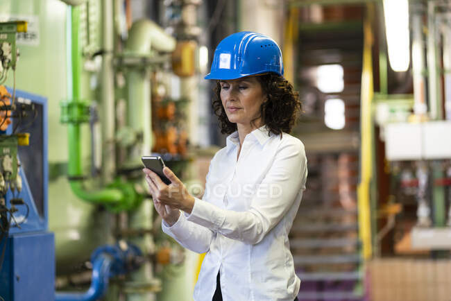 Female engineer with hardhat using mobile phone while standing in industry — Stock Photo
