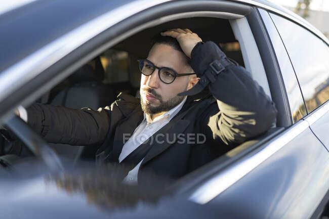 Homme entrepreneur avec la main dans les cheveux regardant loin tout en conduisant voiture — Photo de stock