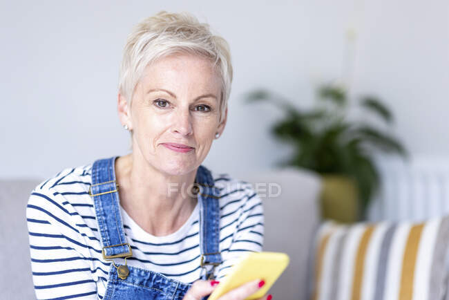 Woman with smart phone at home — Stock Photo